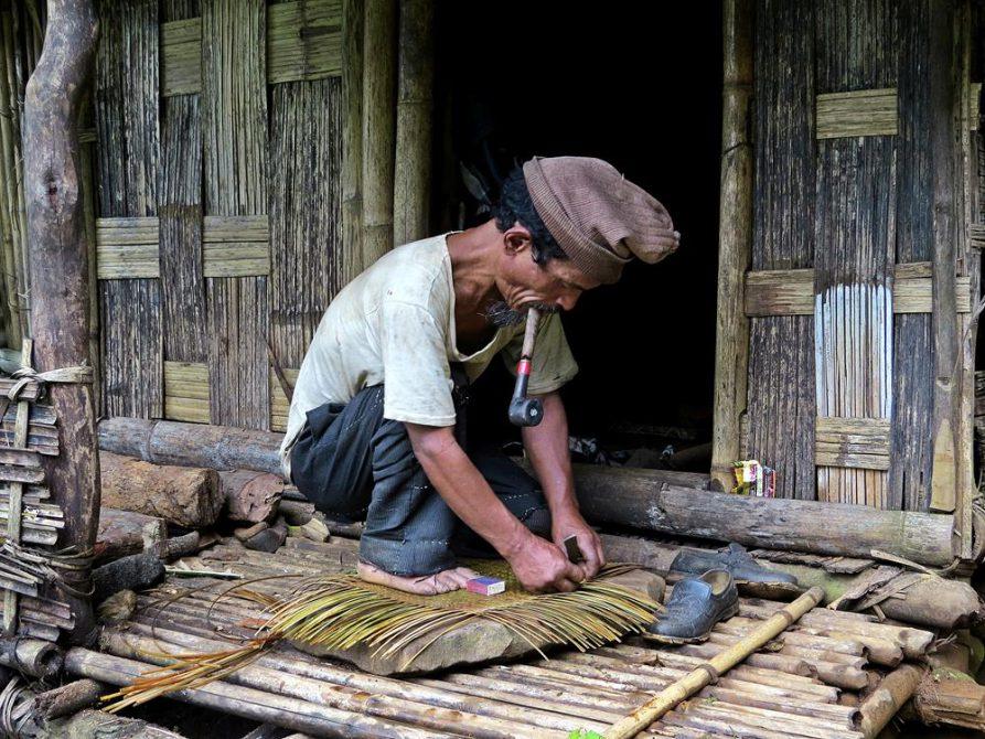 Mann flechtet vor seiner Hütte, Kongthong, Indien