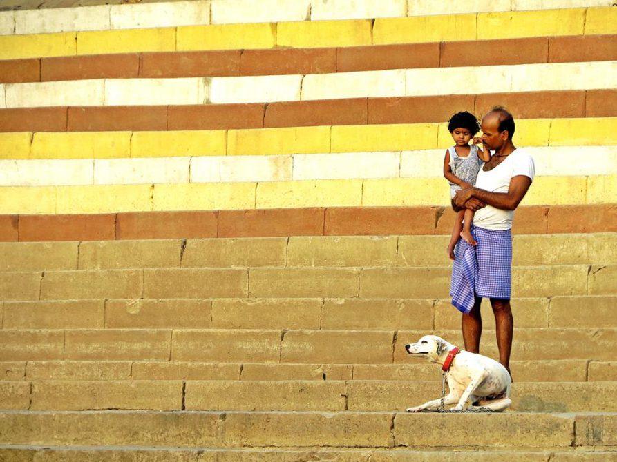 Mann mit Kind auf dem Arm und Hund, Varanasi, Indien