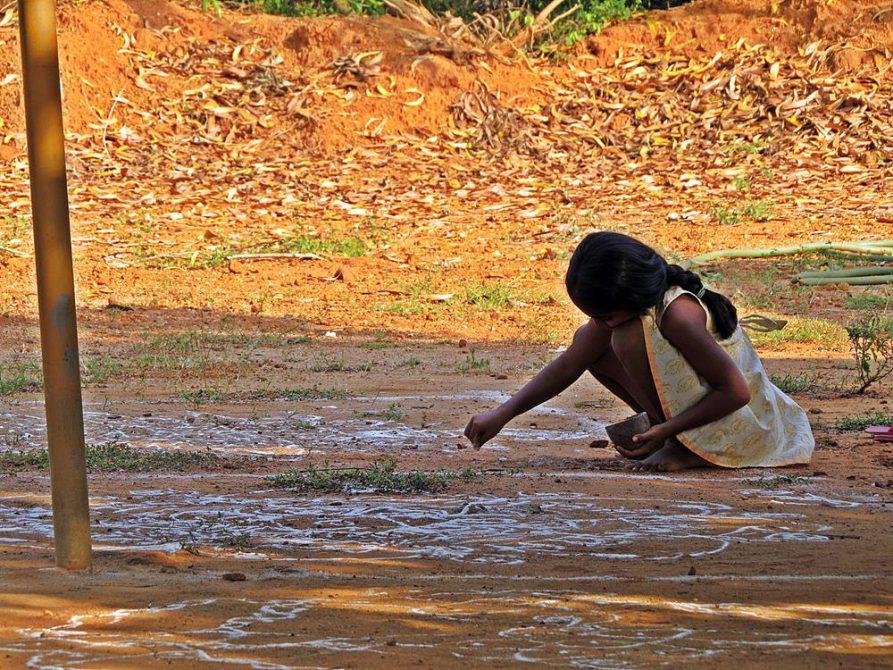 Mädchen zeichnet Mandala auf den Boden, Auroville