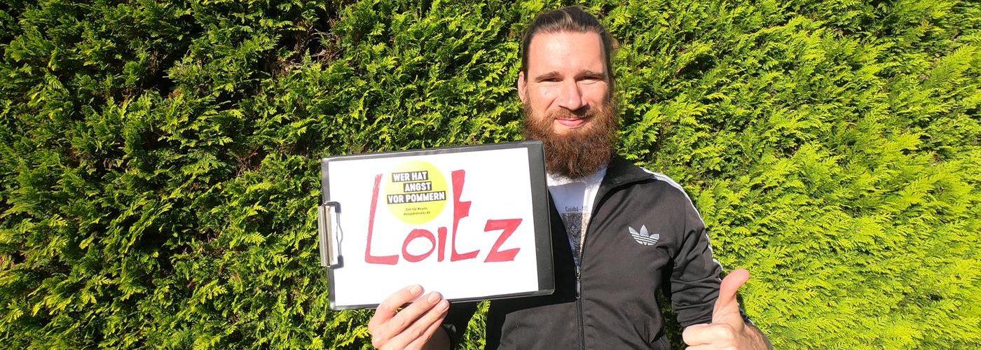 Loitz, Mann mit Schild, Titel