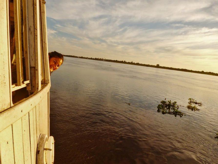 junge Frau schaut aus einem Schiffsfenster