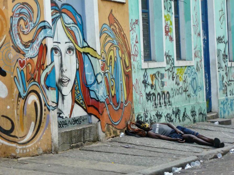 Mural und schlafende Person auf Bürgersteig in Lapa, Rio de Janeiro